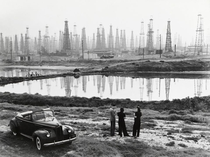 A forest of oil derricks makes a ghostly backdrop for a conversation in Signal Hill, California, in 1941. The city is located north of Long Beach in Los Angeles County. The complex geology of the L.A. Basin caused massive amounts of oil to be trapped beneath the city, which fed a booming oil industry at the turn of the century. At their peak, the wells at Signal Hill led California oil production.  Photograph by B. Anthony Stewart, National Geographic: Oil Fields, Signals Hill, Long Beaches, Oil Derrick, National Geographic, Oil Rigs, The Angel, Anthony Stewart, Oilfields