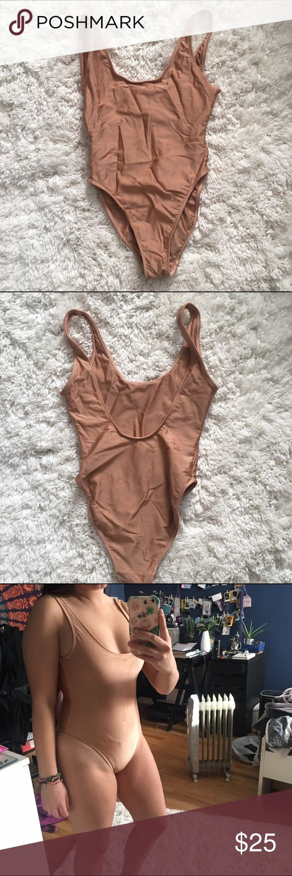 American Apparel nude one-piece swimsuit Literally such an awesome and trendy swimsuit from AA!!! Really pretty blush nude color. Made from a metallic-y tricot fabric. Low cut with a plunged scoop back. Unlined and not padded, but thick material. Fits A and B cup best since it is pretty tight. Also can be worn as a bodysuit with some shorts!! Sorry that it is so wrinkly in the pictures lol, will cool iron before shipping. American Apparel Swim One Pieces