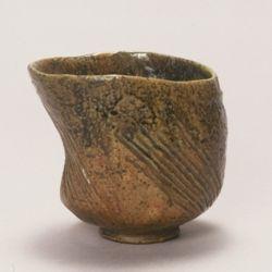 初代長左衛門(1631-1712)作 大樋飴釉茶碗 銘「聖」/Hijiri (Saint) Tea Bowl, Ohi amber glaze made by Ohi Chozaemon I 裏千家十五代家元 鵬雲斎(1923-) 箱 九代大樋長左衛門(1901-1986) 箱 Urasenke 15th Hounsai Signed 9th Ohi Chozaemon Signed 初代長左衛門の作品の中でもとりわけ変化に富んだ姿の茶碗である。胴部の一方に弓形の大きな反りをつけ、見込みは深く、一体に薄手に仕上げらている。胴部の三方や高台脇の二方につけたれた櫛目状の荒々しい箆目や全面に薄く施された飴釉、畳み付けの細い小振りな高台など初代長左衛門の特色が随所に見られる。飴釉は一部に青味を帯び、胴の一部には黒色の窯変があらわれている。同じ手びねりで成形であっても楽家とは異なった大樋焼独特の作風が示された一碗ということができる