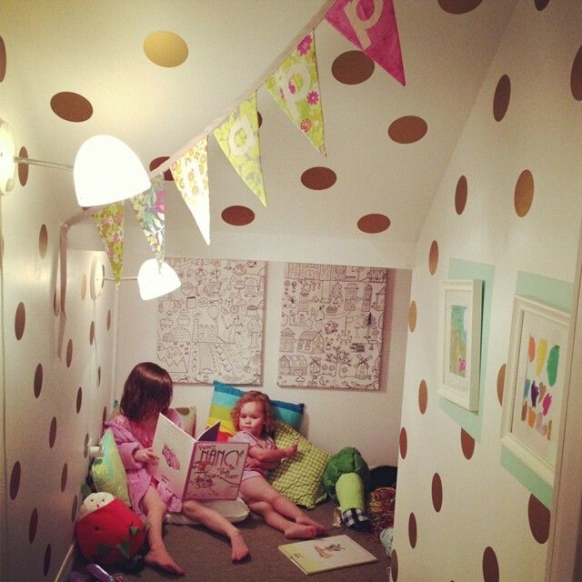 Polka dot vinyl stickers on a beige wall in a girl's playroom. Two girl's are hanging out together in the room reading.