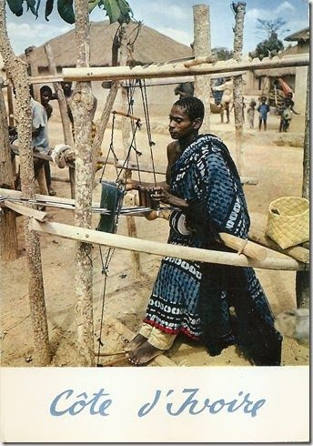 Vintage postcard, postmarked 1969, showing a Baule or Dioula weaver in Côte D'Ivoire, wearing an indigo overdyed robe cloth and weaving an ...