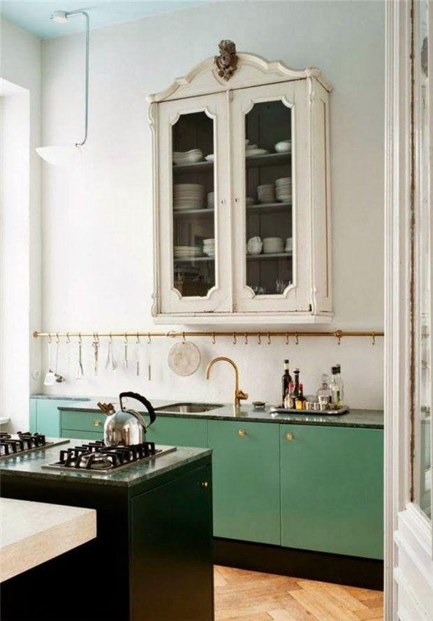 Sobre uma base branca, foram adicionados elementos contrastantes entre si que casam muito bem. Para guardar os pratos, foi eleito um armário vintage de curvas elaboradas. Já a pia minimalista ganhou o frescor do verde e o bilho do dourado.