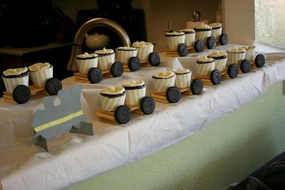 cupcakes (free printable cupcake wrappers below).  Chocolate with buttercream frosting.  Arranged like a little train that I built out of vanilla sugar wafers, graham crackers, and Oreos
