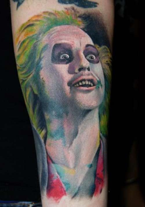 Beetlejuice Tattoo:  This is a picture of Beetlejuice, a character from a 1980s movie, played by Micheal Keaton. It is tattooed on someone's arm. In the image, Beetlejuice it looking to his left and upwards. His hair is green and appears to be receding. His eyes have dark circles around them and there is a spot of green on is mouth. The image is a bust portrait only.