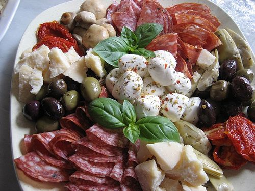 Gorgeous composed Antipasto salad plate of mozzarella, salami, olives, peppers, basil, etc