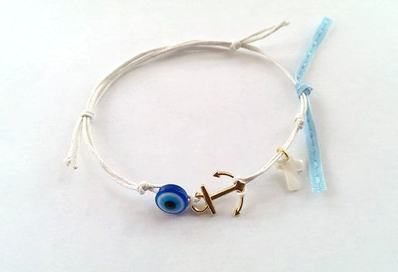 White bracelet with mother of pearl cross and evil eye.