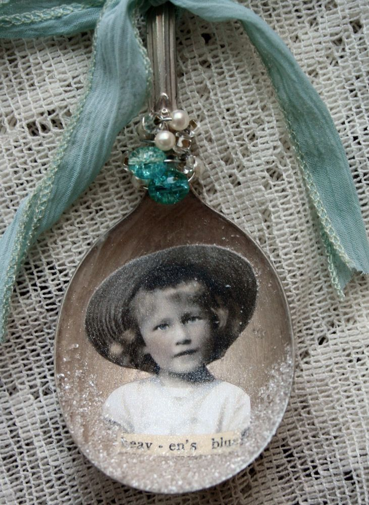 A vintage altered spoon. Bead work, silver charms, German glass glitter, and vintage seam binding ribbon has also been added.