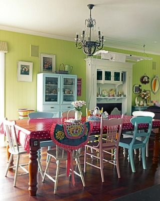 COLOUR THROUGHOUT: An old leadlight painted kitchen dresser blends well with multicoloured kitchen chairs in varying styles; an entire load of laundry fits on the drying rack above the fire surround; otherwise the rack is used to display Sheryl's favourite tablecloths.