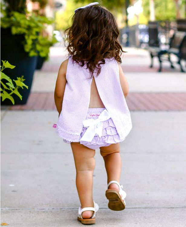 Seersucker is a true staple for any spring and summer wardrobe. This little girls lilac seersucker RuffleButt bloomer is sure to create all the smiles and compliments for your stylish little girl! Pair with our Lilac Seersucker swing top and bow headband for a complete outfit that'll make you swoon.