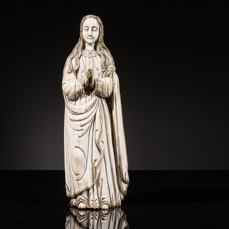Importante Vierge en ivoire sculpté en rondebosse avec rehauts de dorure. Debout, les mains  jointes, elle est vêtue d'une robe au col orné de  croix et d'un manteau dont un pan revient sur  le devant retenu par l'avant-bras gauche ; visage  ovale aux cheveux déliés tombant en longues  mèches ondulées sur les épaules.  Indo-portugais, XVIIe siècle  H 39,5 cm #piasa_auction #piasa  #inspiration  #paris  #collectors #youngcollectors #hauteepoque