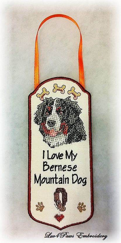 """This Bernese Mountain Dog Door Hanger design is machine embroidered in a cross stitch style. This can also be displayed as a Wall Hanging. """"I Love My Bernese Mountain Dog"""". Size: 3"""" wide x 7"""" tall, not including the ribbon hanger, which makes it approximately 11"""" inches tall when hanging. Wording can be customized. by Luv4PawsEmbroidery"""