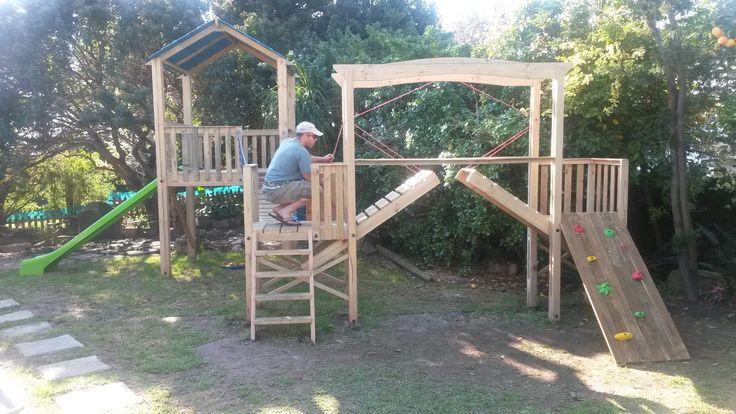 Joshua's Joy A play structure with slide, swing bridge, climbing wall and draw bridge.