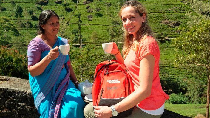 Tamina Kallert sitzt mit einer weiteren Frau auf einer Mauer und trinkt Tee | Bildquelle: WDR/Per Schnell
