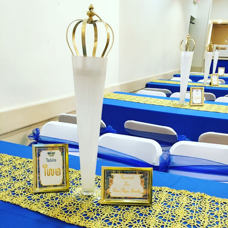 Crown Centerpieces On A Gold Runner With Blue Tablecloths