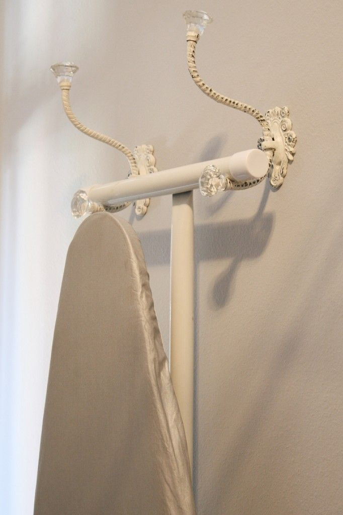 Two beautiful metal coat hooks for the wall repurposed to hold an ironing board | Laundry Room Organizing Ideas