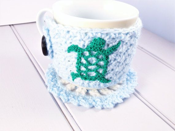 This cute sea turtle mug sweater is the perfect housewarming gift, especially if theyre coffee and tea lovers! It comes with a matching coaster, making a really great gift set. It has been crocheted in a pretty pale blue colour with a green lace sea turtle, gender neutral colours that anyone is sure to love. It will keep your drink warm and stop your hands from burning when holding your mug, perfect for cosy nights in. The cosy itself is made using acrylic yarn so is very soft, and has a…