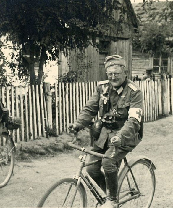 German soldier-Medic rides on bike. Better a bad ride-than good to go.