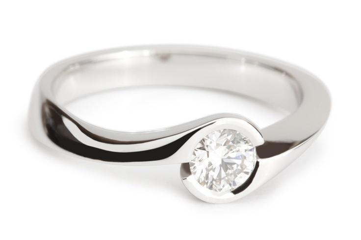 Verlovingsring Venice. De sierlijke scheen van deze verlovingsring krult om de diamant heen en vormt zo een zetkast waarin de diamant prachtig tot zijn recht komt. Het golvende lijnenspel van de ring geeft de verlovingsring een unieke uitstraling. De verlovingsring Venice is uit te voeren met een diamant formaat naar keuze.