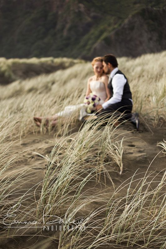 Magical golden hour lighting in this Bride and Groom shot in the sand dunes at Karekare beach, West Auckland. A 20 minute drive through the Waitakere Ranges from Titirangi Village. www.emmabaker.co.nz