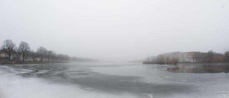 [5183x2228] An ice covered Sortedams Sø in Copenhagen viewed from Østerbrogade towards Fredens Bro enveloped in dense fog