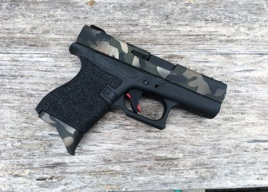 Glock 43  A customized example of the single-stack 9x19mm pocket pistol made by Glock, which received a lot of fanfare when it was introduced to the market. Aside from the finish on the slide and magazine floorplate, it appears to have an aftermarket trigger, sights and a stippling job applied to the grip.