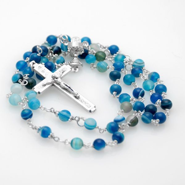Azurine Gemstone Holy Communion Rosary For Boys & Girls - This stylish 1st Holy Communion rosary is crafted with 6mm blue banded agate semi precious . The 'Our Father' beads are 6mm blue agate with a silver plated daisy bead on either side.  Each bead is hand wrapped with tarnish resistant silver plated wire using the traditional wire wrapping technique.  The centerpiece medal is a beautiful pewter chalice and host and the design is finished with a pewter scroll crucifix measuring 4cm by…