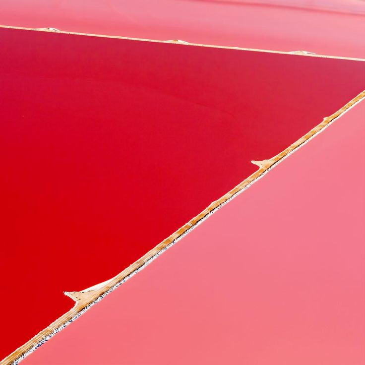 Steve Back's Hutt Lagoon photography  - taken from an aircraft while traveling over Hutt Lagoon in Kalbarri, Western Australia.  Captured over the course of three years, the un-doctored photos are a striking representation of the largest micro algae production plant in the world.  Reflecting hues from bright orange to hot pink, the seemingly un-natural colors are the fortunate consequence of an organically produced beta carotene in the water— so vibrant it's sourced as food coloring.