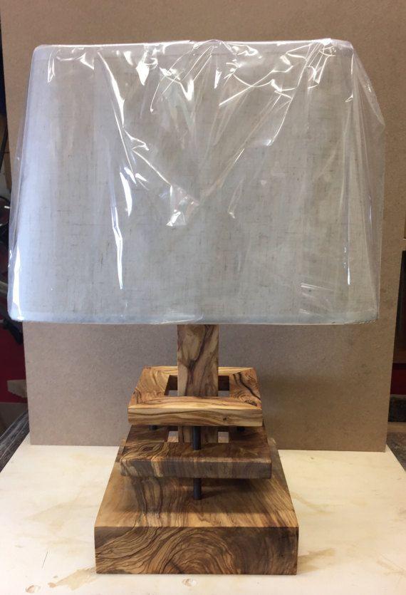Lámpara de mesa o escritorio en madera de olivo con pantalla de tela. La madera ha sido tratada con aceite natural sin cualquier solvente y no tóxico. La sombra en la foto todavía se embala en su celofán protector. El cable de alimentación puede ser gris o rojo.
