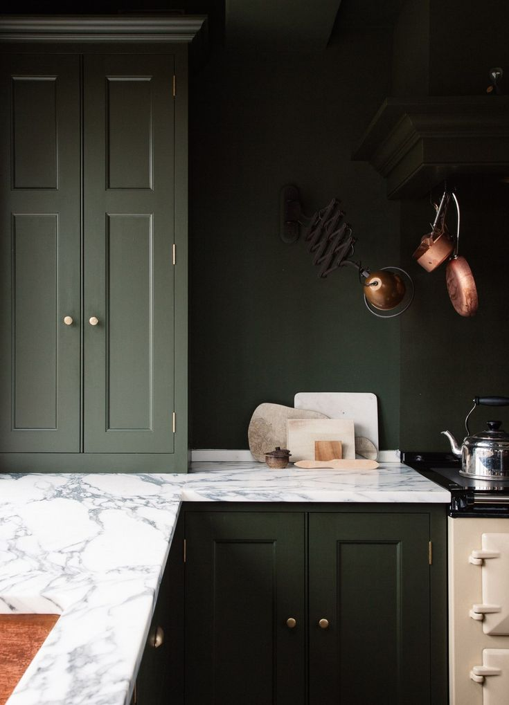 The centerpiece of the space: a vintage-style, oil-fueled Aga range in a cream color. (See Design Sleuth: Classic Aga Cookers.) In keeping with the homeowners' request for a variety of materials, the main countertops are honed Arabescatto marble with gray-green veining. Vintage copper pans hang above the stove. (Note how the deep green background throws artful kitchen tools into stark relief.)