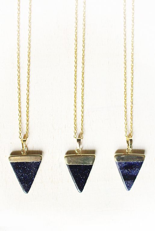 Guldpläterat halsband med en triangelformad berlock av blå-svart guldsten. | Gold plated necklace with a triangle-shaped pendant of blue-black gold stone.