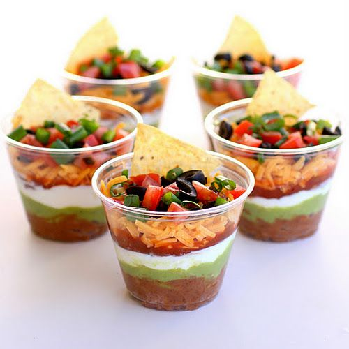 Individual Seven-Layer Dips  Makes about 8 individual dips  Ingredients:  1 (16 ounce) can refried beans  1 (1 ounce) package taco seasoning  1 cup guacamole   1 (8 ounce) container sour cream   1 cup chunky salsa   1 cup shredded cheddar   2 Roma tomatoes, diced   1/2 bunch of green onions, sliced   1 (2.25 ounce) can of sliced olives, drained   9 ounce plastic tumblers   tortilla chips