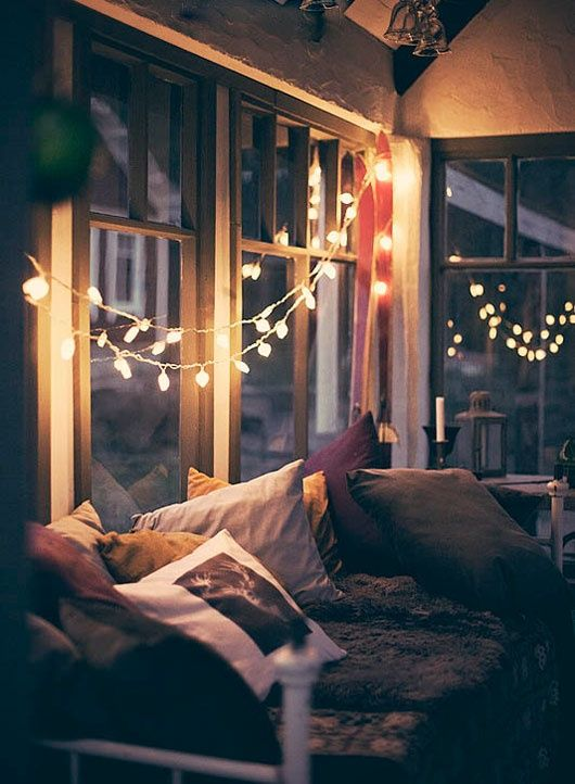 Window seat nook with a simple string of lights and lots of pillows and blankets