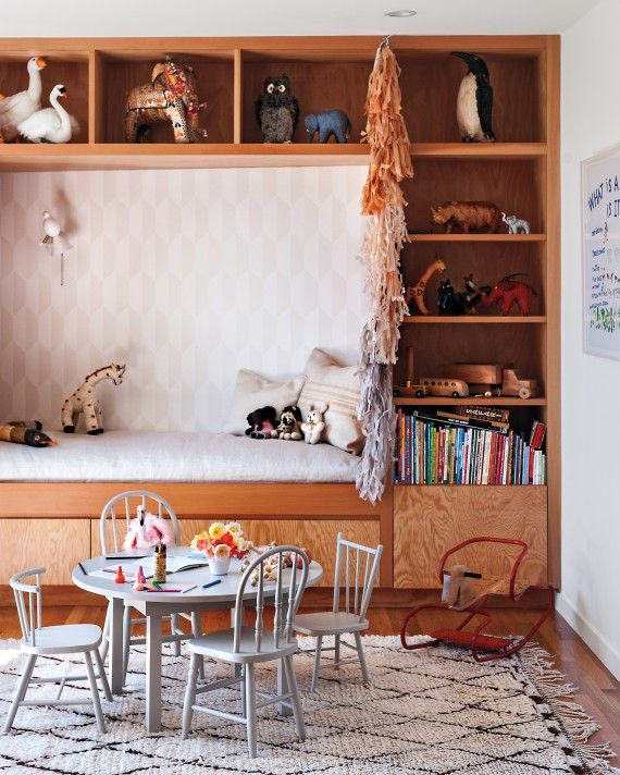 """James's playroom had an angled wall the couple didn't like, so they built a wall unit with a daybed and bookshelves to square it off. """"It's such a cozy spot to read with James,"""" de Ruiter says. They unified mismatched children's chairs they'd collected at various flea markets with a coat of paint. Lind made the table."""
