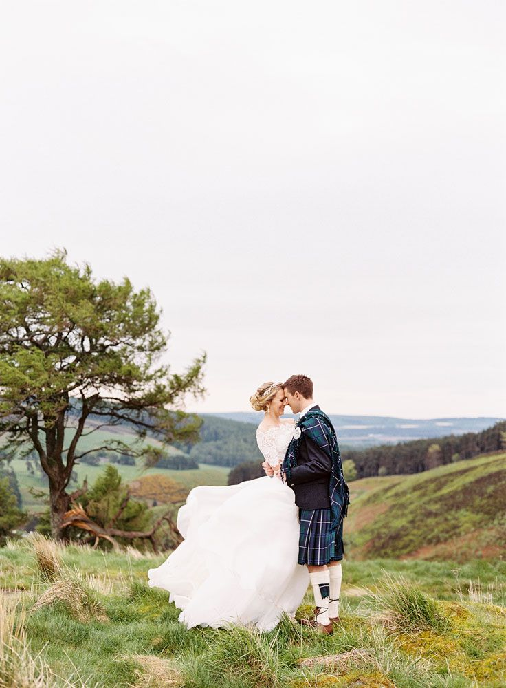 Bride & Groom portrait on the picturesque Scottish Mountains - Image by Ann-Katherin Koch Photography - Caroline Castigliano dress for a classic fairytale wedding in a Scottish Castle. Groom in Tartan Kilt and Bridesmaids in BHLDN dresses.