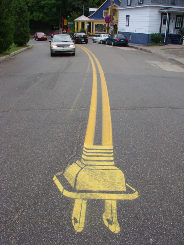 Street art :- it's so funky because heshe used the yellow line in the street to make the wire