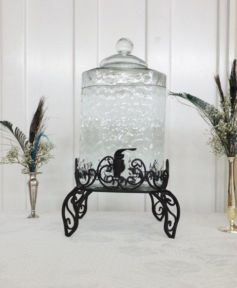 Water for guests with peacock feathers in silver vases.