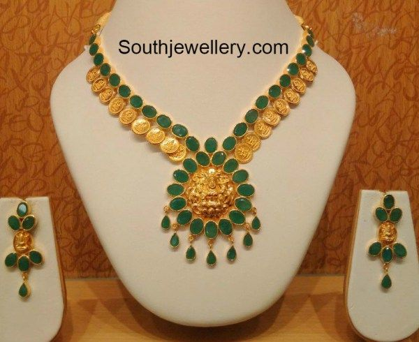 22 carat gold Lakshmi kasu necklace studded with emeralds paired with suitable earrings.