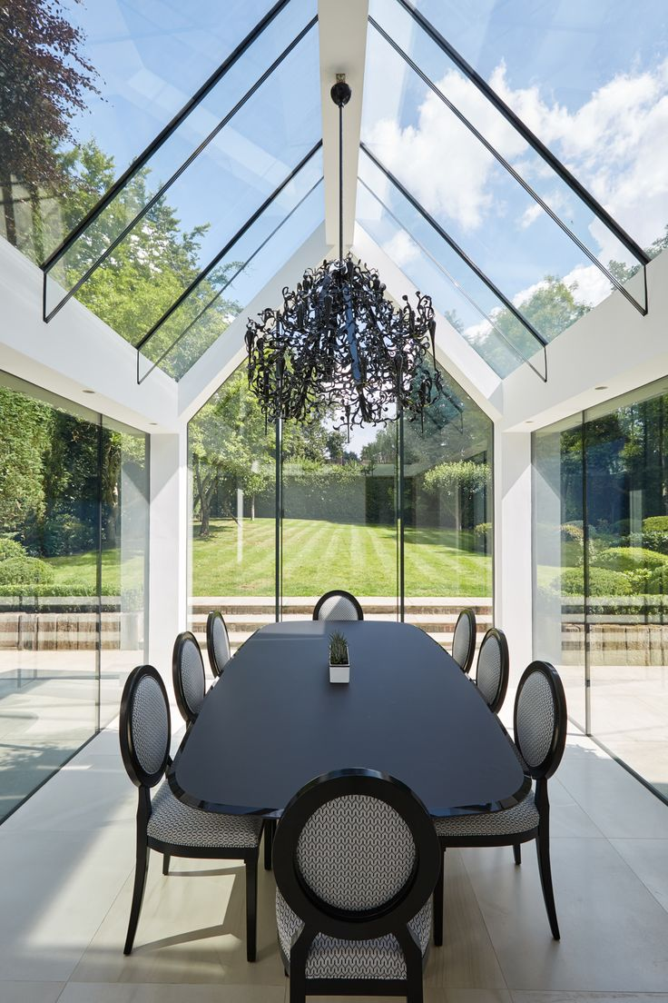 Contemporary white dining room with a structurally glazed roof, glass beams and gable wall