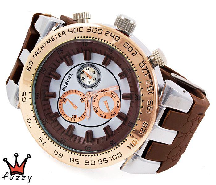 Γυναικείο ρολόι, με κάσα σε ροζ χρυσό και ασημί και ανάγλυφα καφέ σχεδια  στο εσωτερικό του.  Λουράκι σε καφέ χρώμα από σιλικόνη. Διάμετρος καντράν 47 mm
