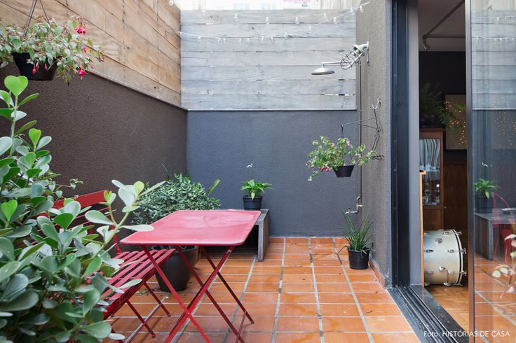 Área externa do apê tem meia parede preta e divisória de madeira para dar mais privacidade em relação ao apie vizinho.