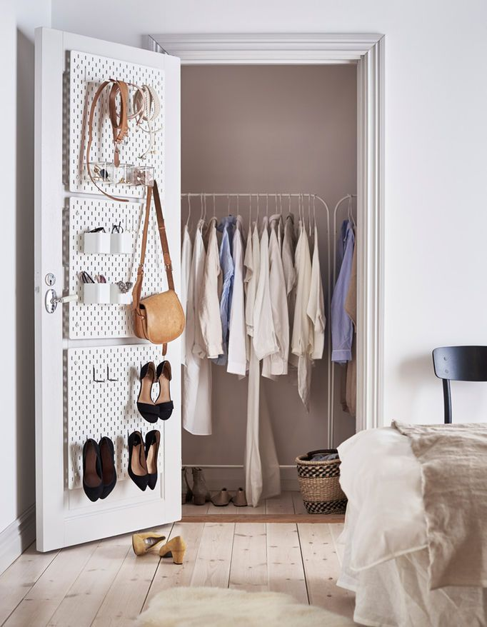 White SKÅDIS pegboards attached to the inside of a closet door to organise accessories and shoes