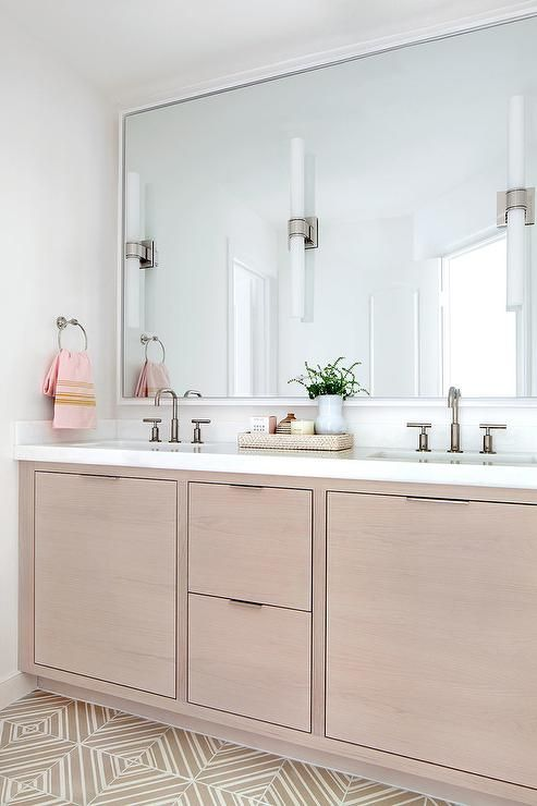 Three white glass and dark nickel sconces are mounted on a white framed full length mirror fixed to a white wall above a beige oak dual washstand framed by by beige mosaic floor tiles and topped with a white quartz countertop fitted with sinks paired with dark nickel faucet kits.