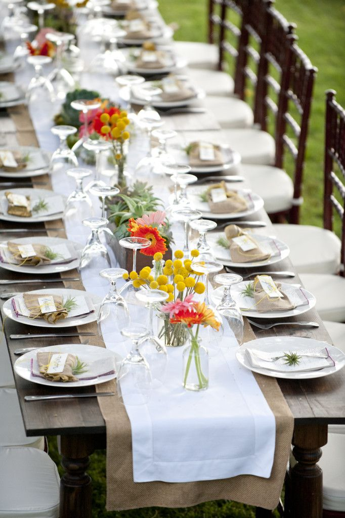 A burlap and white table runner ran along the center of the dark wooden table, subtly showcasing the rustic details– soft green succulents and moss beds beautifully offset by pops of orange and pink dahlias and bright yellow billy buttons