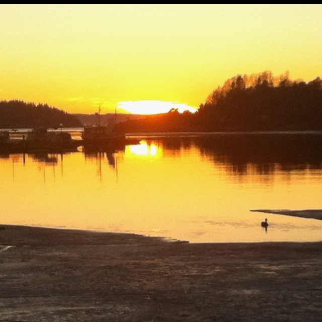 Son, Norway 28.02.2012 The fjord ice is melting and sun sets at 6pm.