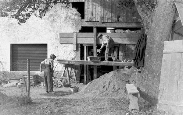 Maçons en train de réaliser une ouverture. Il semble que le linteau ait été fait en béton (coffrage et étaiement visibles). Le maçon est en train de rebâtir en pierre par dessus.