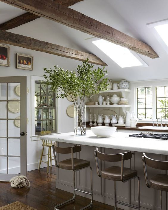 Gorgeous white and wood beamed kitchen with natural foliage in a vase.