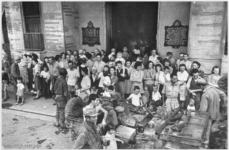 Освобожденные американские и филиппинские заключенные у главного входа в университет Санто-Томас, который был использован в качестве японского лагеря, прежде чем союзные освободительные силы вошли в город. Манила, Лусон, Филиппины. 5 февраля 1945 г.