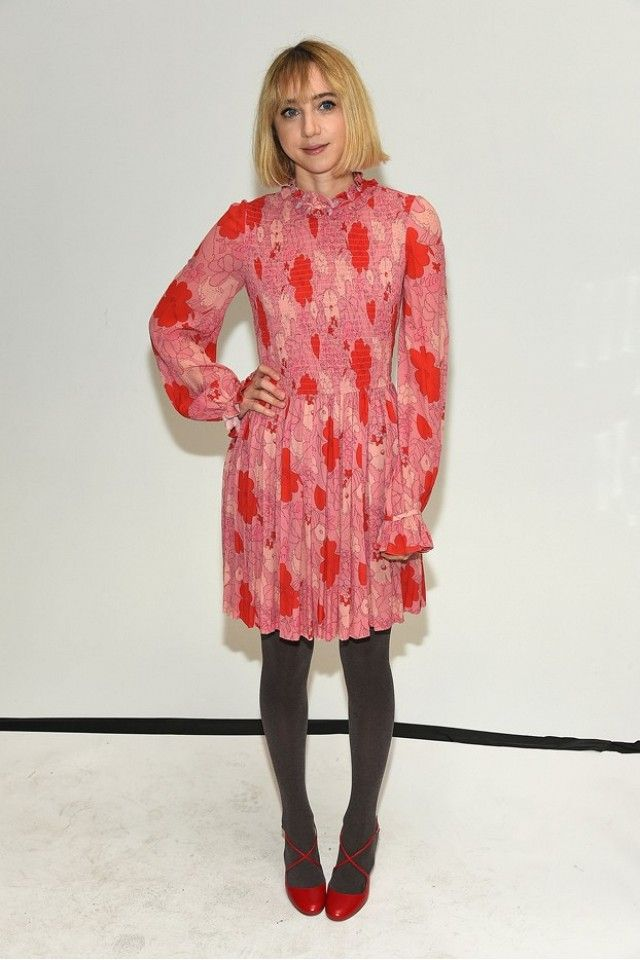 Zoe Kazan wears a floral pink and red high-neck mini dress with tights and red heels