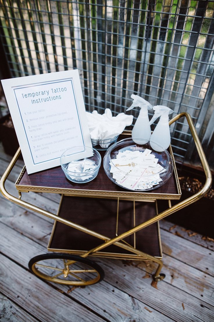 Wedding Ideas: Temporary Tattoo Station! Brass Mid-Century bar cart used for a fun temporary tattoo station at a wedding. Rentals by Birch & Brass Vintage Rentals.