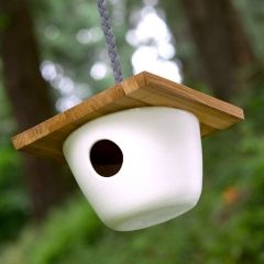 """bird house: Hand-thrown porcelain base with a handmade paneled cedar roof and an 18"""" long grey braided leather cord for hanging."""